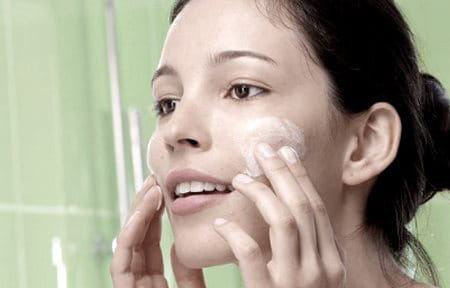 Image of woman applying Eucerin Scrub to her face