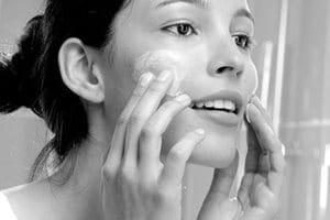 Woman appliying cream on her face""