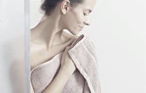 Woman patting her skin dry after showering,